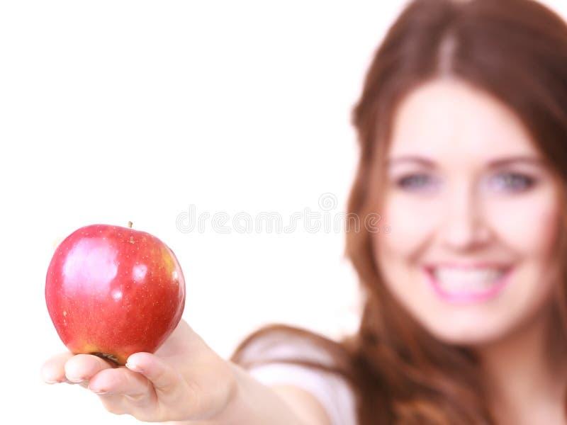 Kvinnan rymmer det r?da ?pplet, fokus p? frukt arkivbild