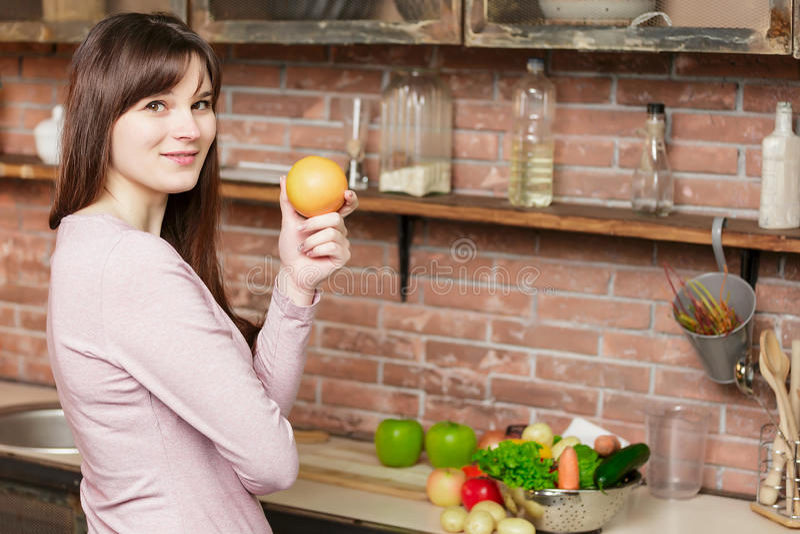 Kvinnan rymmer en apelsin i hennes hand Matlagning för ung kvinna i köket hemma sund mat banta royaltyfria foton