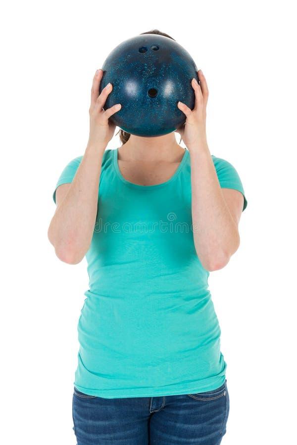 Kvinnan rymmer en bowlingklot precis för hennes huvud royaltyfri bild