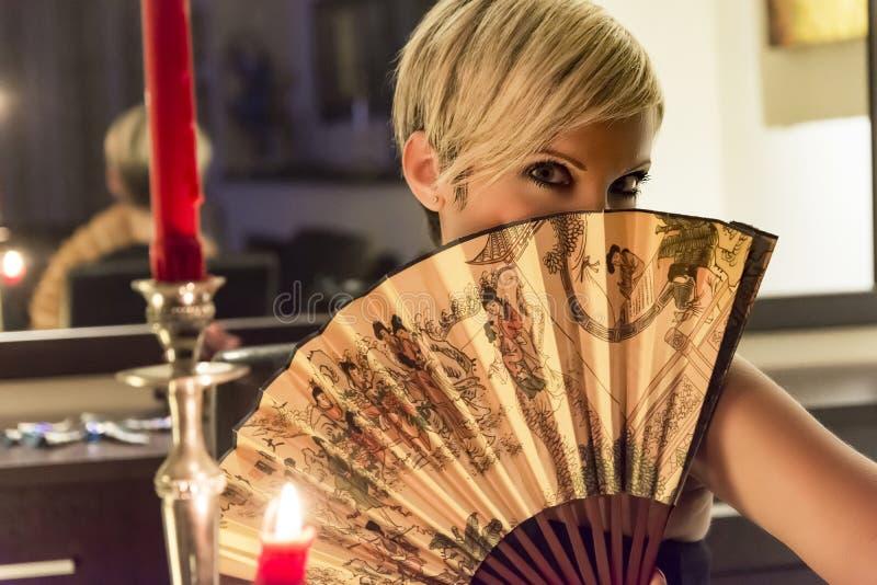 Kvinnan rymmer en fan royaltyfri fotografi