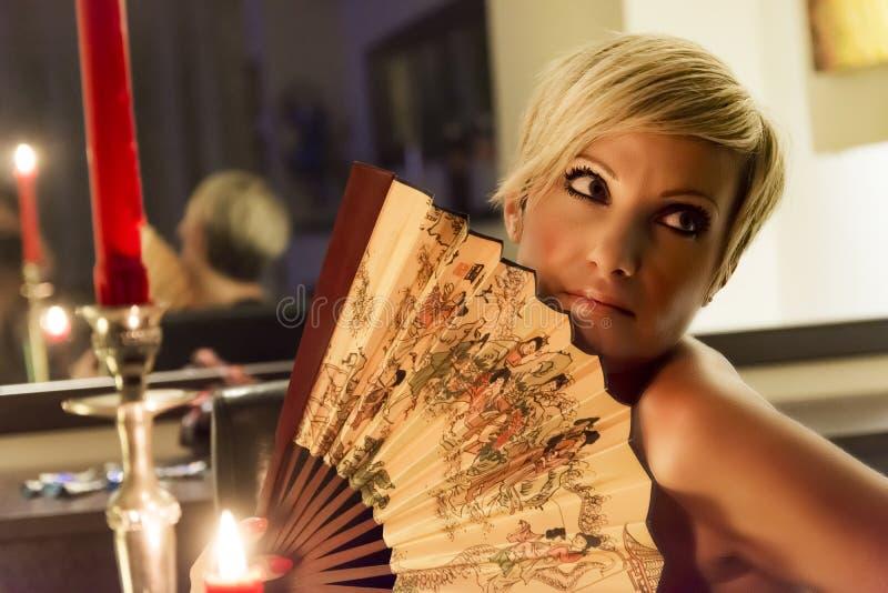 Kvinnan rymmer en fan arkivfoto