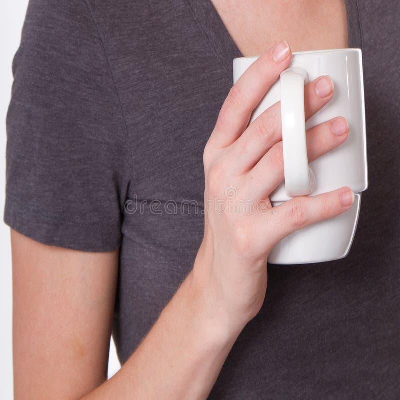 Kvinnan rymmer en kopp kaffe arkivfoton