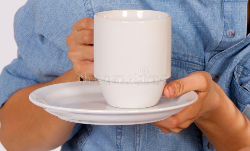 Kvinnan rymmer en kopp kaffe arkivbild