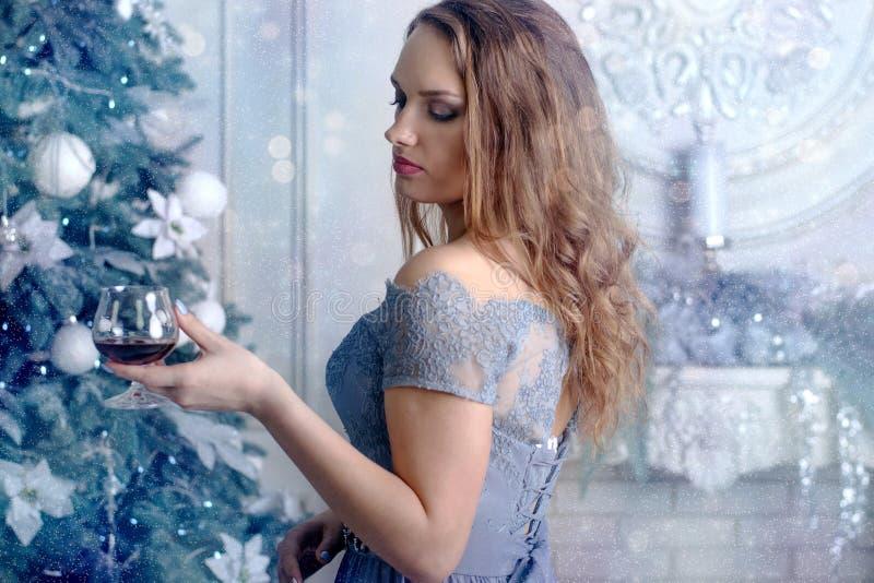 Kvinnan rymmer ett exponeringsglas av konjak arkivfoto