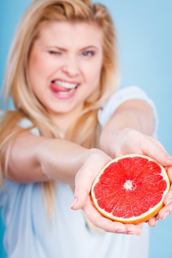 Kvinnan rymmer grapefruktcitrusfrukt i händer royaltyfri foto