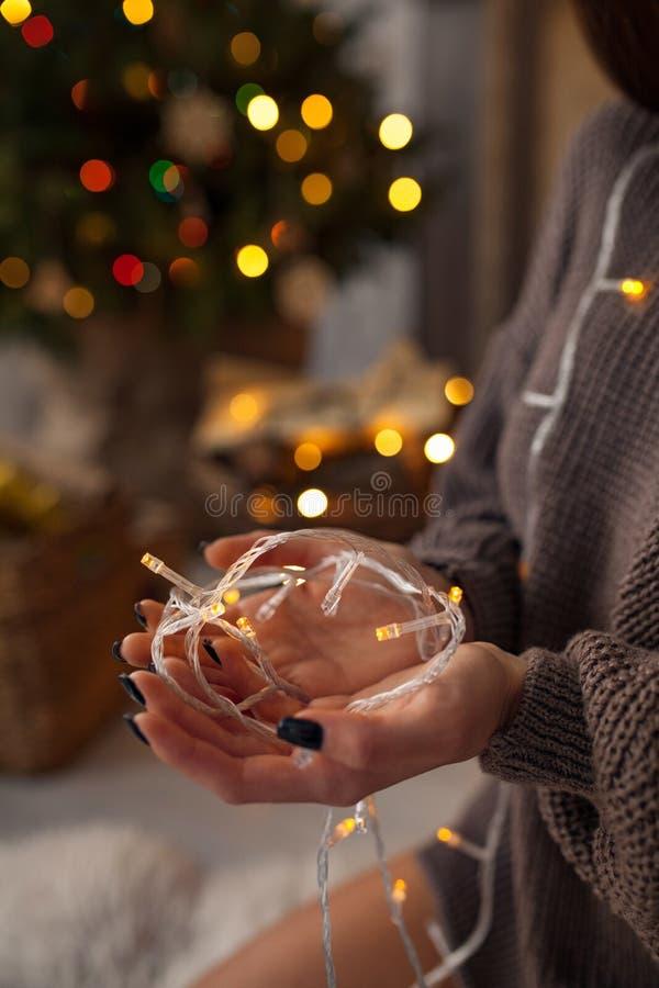 Kvinnan rymmer lightbulbgirlanden i hennes händer på bakgrund av julljus closeup arkivbilder