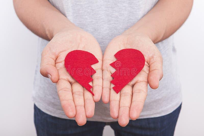 Kvinnan rymmer mycket liten röd hjärta undertecknar in händer på vit bakgrund fotografering för bildbyråer