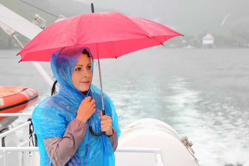 Kvinnan rymmer paraplyet på det små fartyget arkivbild