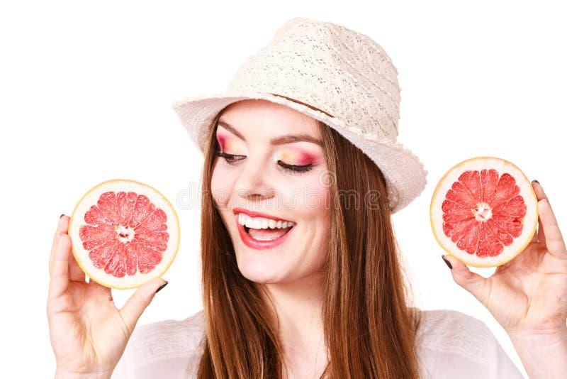 Kvinnan rymmer två halfs av grapefruktcitrusfrukt i händer arkivbild