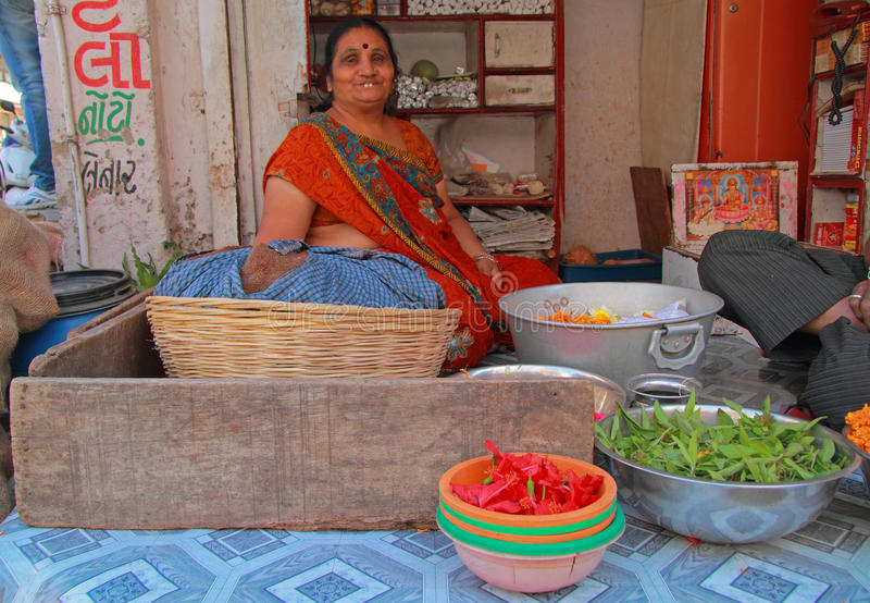 Kvinnan säljer örter som är utomhus- i Ahmedabad, Indien arkivbild