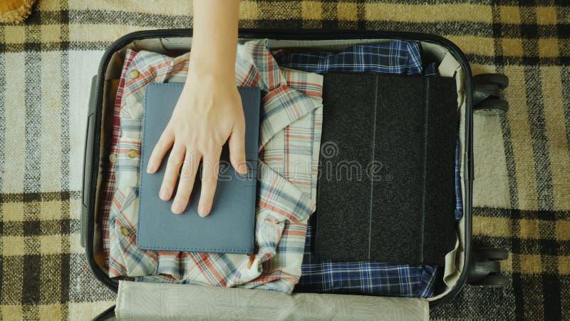 Kvinnan sätter en anteckningsbok i en loppresväska royaltyfria bilder