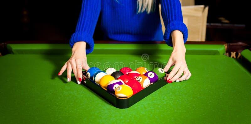 Kvinnan sätter en pyramid av bollar för en pöl på en billiardtabell arkivbild