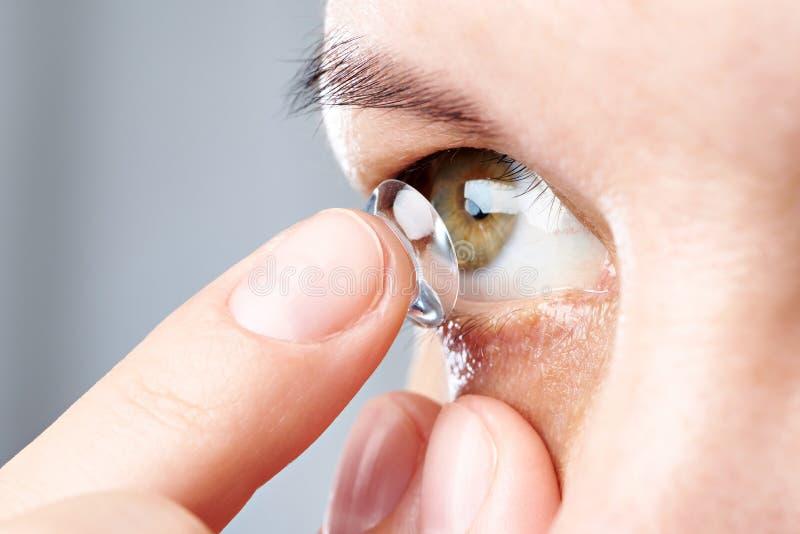 Kvinnan sätter kontaktlinsen arkivbild