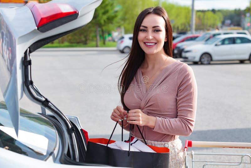 Kvinnan sätter påsar från shoppingvagnen till stammen royaltyfri fotografi