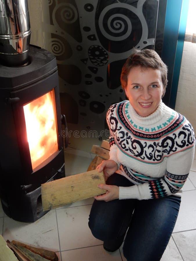 Kvinnan sätter trä i spis arkivbild