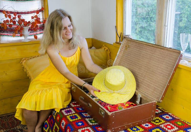 Kvinnan satte den trevliga gula hatten i gammal resväska i rum royaltyfri foto