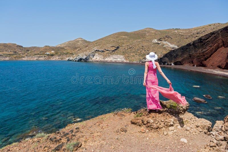 Kvinnan ser den röda stranden i Santorini, Grekland arkivbilder