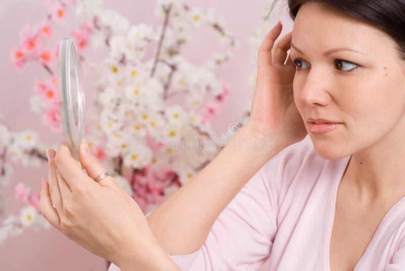 kvinnan ser i spegeln arkivfoton