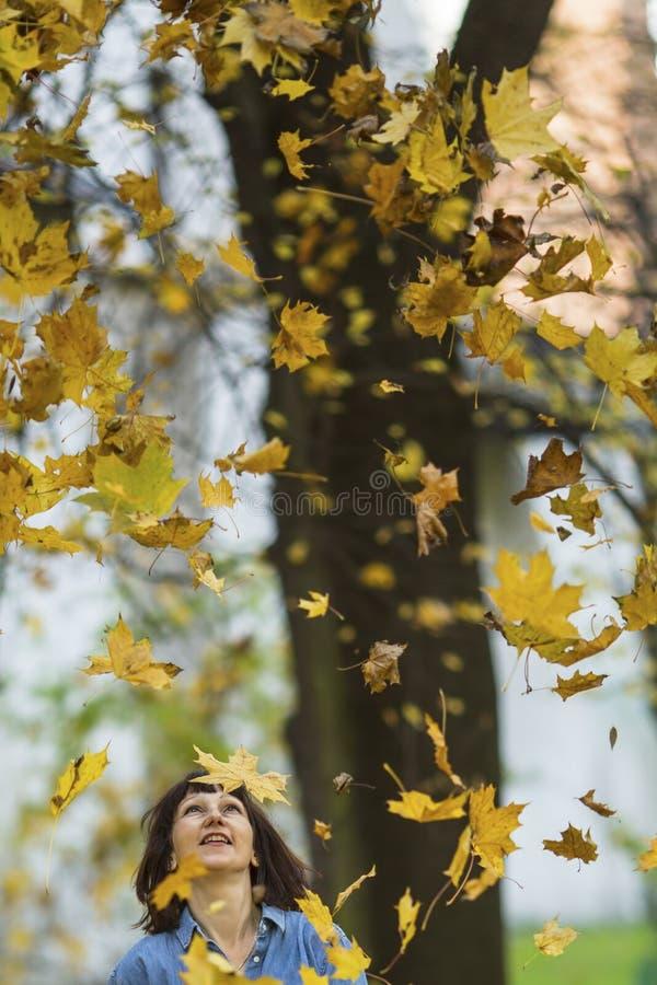 Kvinnan ser på de fallande sidorna i hösten parkerar upp Gå royaltyfria bilder