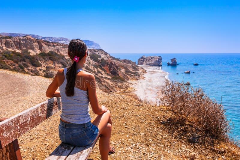Kvinnan ser på den panorama- landskapPetra-touen Romiou vaggar av greken, aphrodite'sens legendariska födelseort i Paphos, Cypern arkivfoto