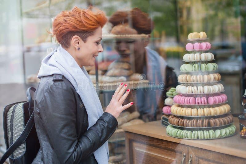 Kvinnan ser ställer ut med färgrika kakor royaltyfria foton