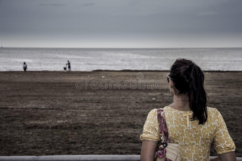 Kvinnan ser stranden arkivfoto