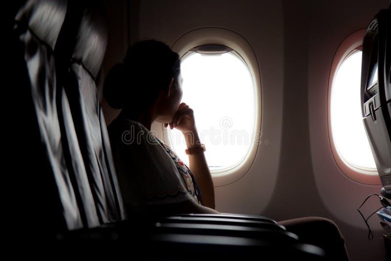 Kvinnan ser ut fönstret av ett flygplan royaltyfri fotografi