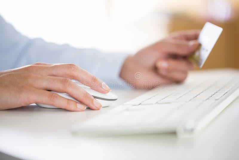 Kvinnan shoppar på internet med datoren arkivfoto
