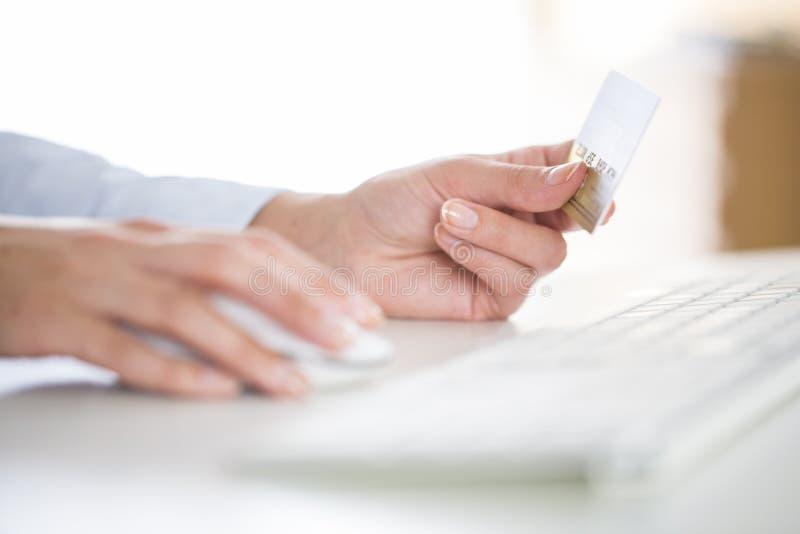 Kvinnan shoppar på internet med kreditkorten arkivbilder