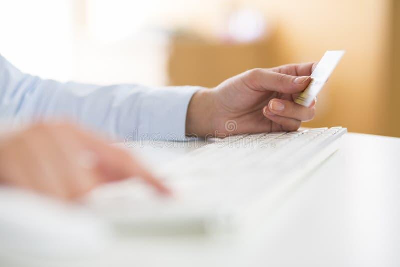 Kvinnan shoppar på internet med kreditkorten arkivfoto