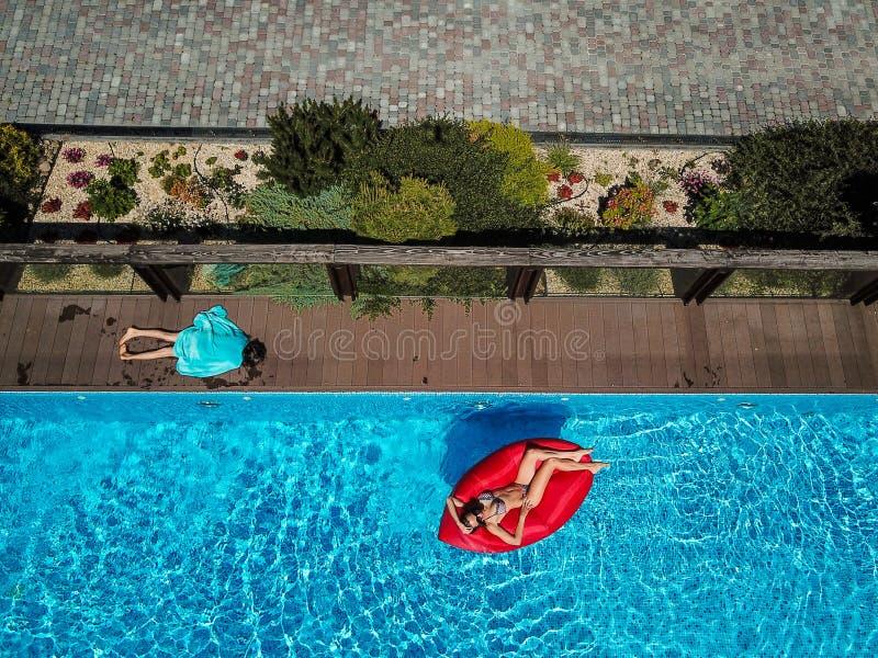 Kvinnan simmar på en uppblåsbar dagdrivare royaltyfri bild