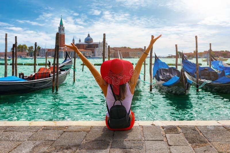 Kvinnan sitter framme av de traditionella gondolerna av fyrkanten för St Mark ` s i Venedig, Italien royaltyfri foto