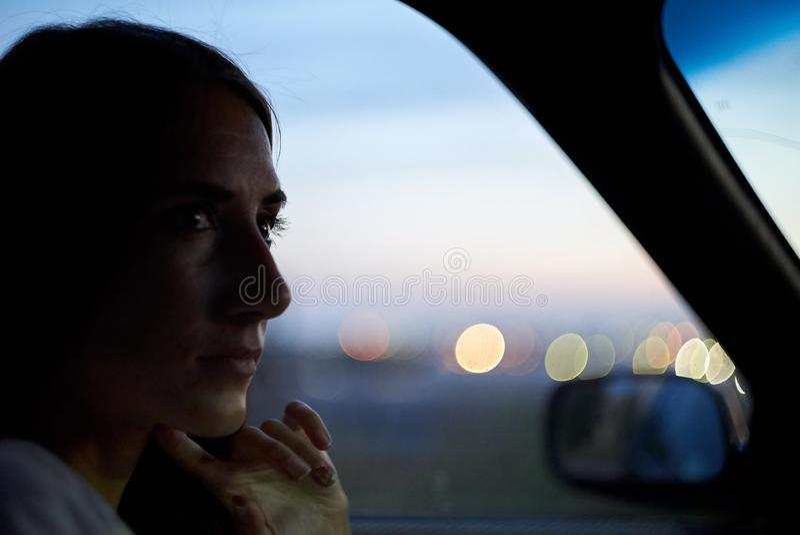 Kvinnan sitter i en bil på stadsljusbakgrunden Aftonnattetid royaltyfri fotografi