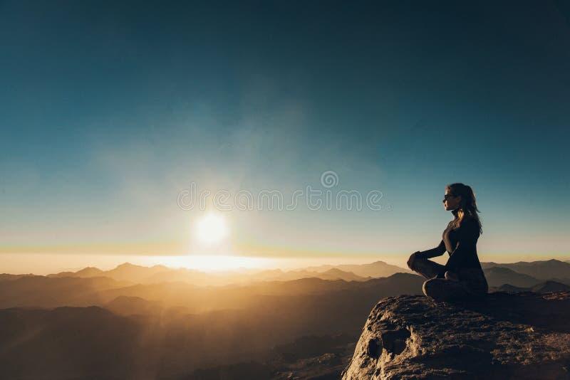 Kvinnan sitter i en posera av yoga på Mount Sinai och mediterar mot bakgrund av soluppgång royaltyfri bild