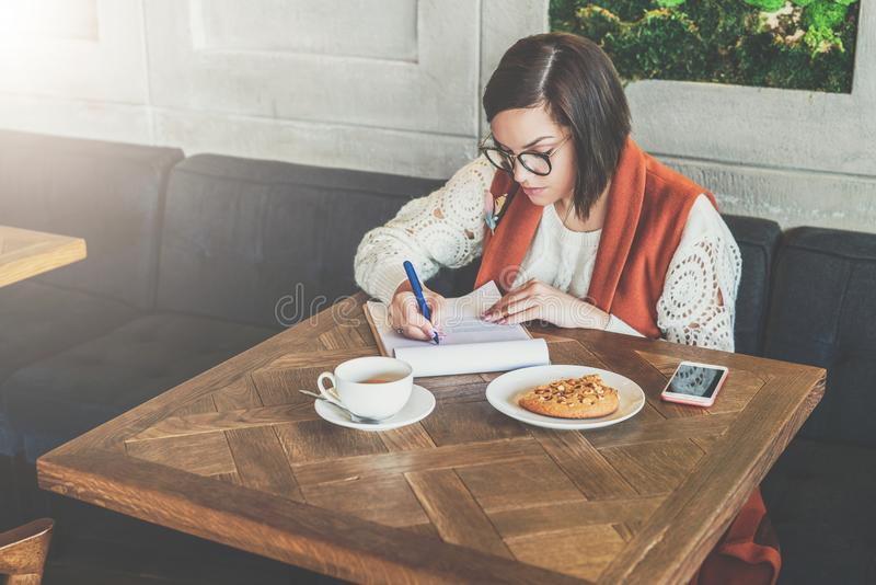 Kvinnan sitter i kafé på tabellen Flickan fyller ut en applikation, frågeformuläret, teckendokument, attraktioner återupptar upp arkivbild