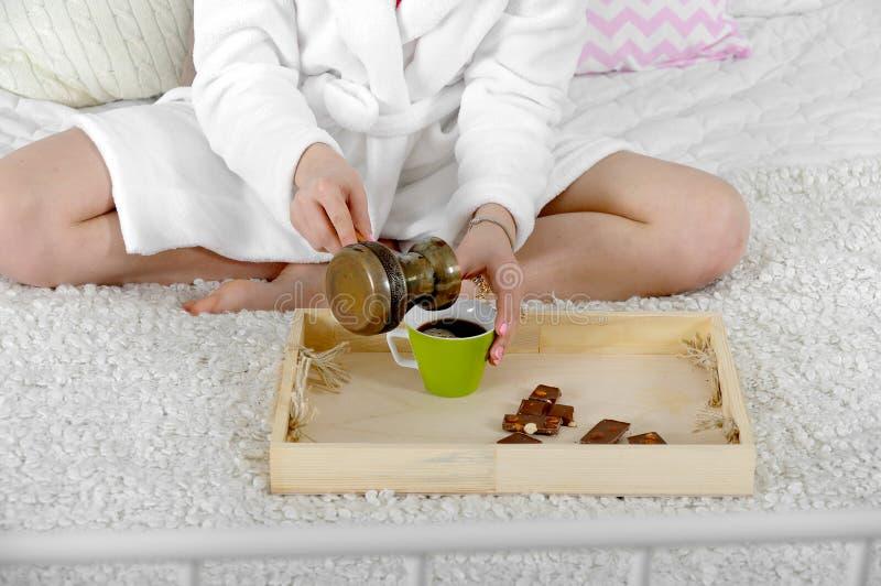 Kvinnan sitter i säng häller kaffekrukor royaltyfria bilder