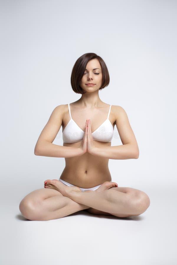 Kvinnan sitter i yoga poserar - lotos arkivfoton