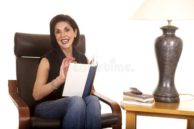 Kvinnan sitter med boken vid lampblick royaltyfria bilder