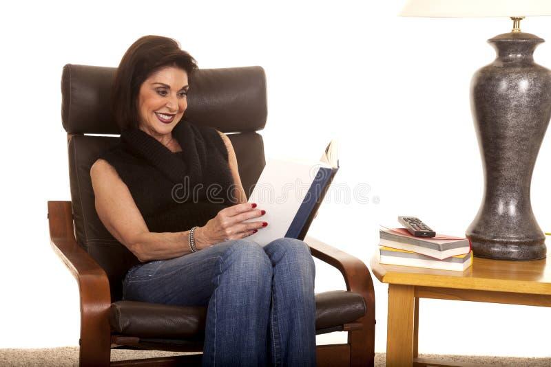 Kvinnan sitter och läste vid lampan arkivfoto