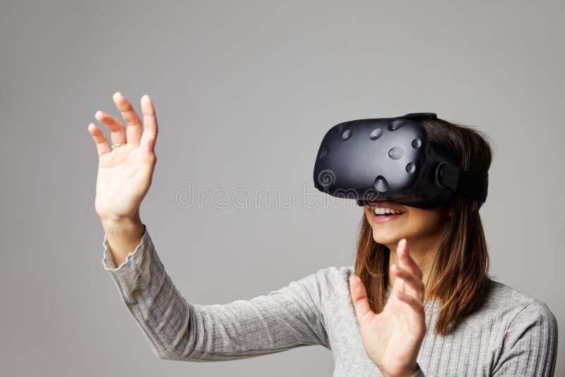 Kvinnan sitter på den Sofa At Home Wearing Virtual verklighethörlurar med mikrofon royaltyfri foto