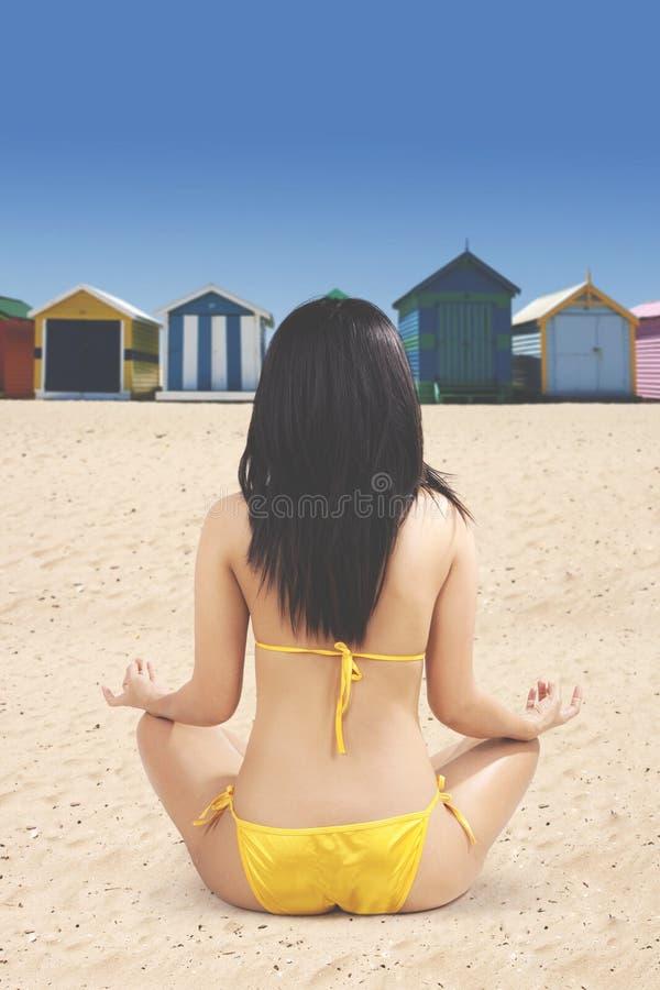 Kvinnan sitter på kusten och att meditera arkivfoto