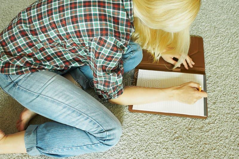 Kvinnan sitter på mattan och skriver arkivbild