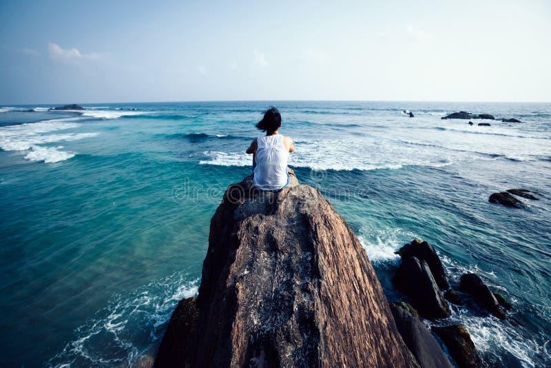 Kvinnan sitter på sjösidan vaggar arkivbilder