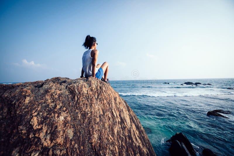 Kvinnan sitter på sjösidan vaggar arkivfoto
