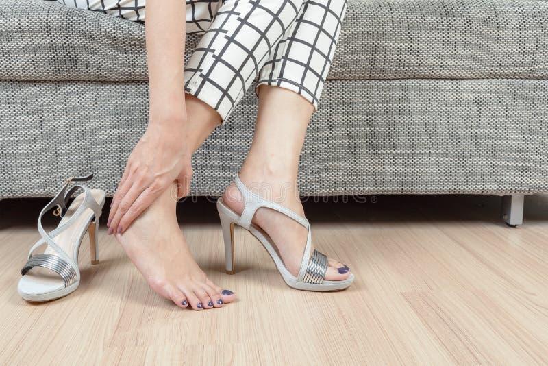 Kvinnan sitter på stol, och den kvinnliga handen med foten smärtar efter, tar sh royaltyfri bild