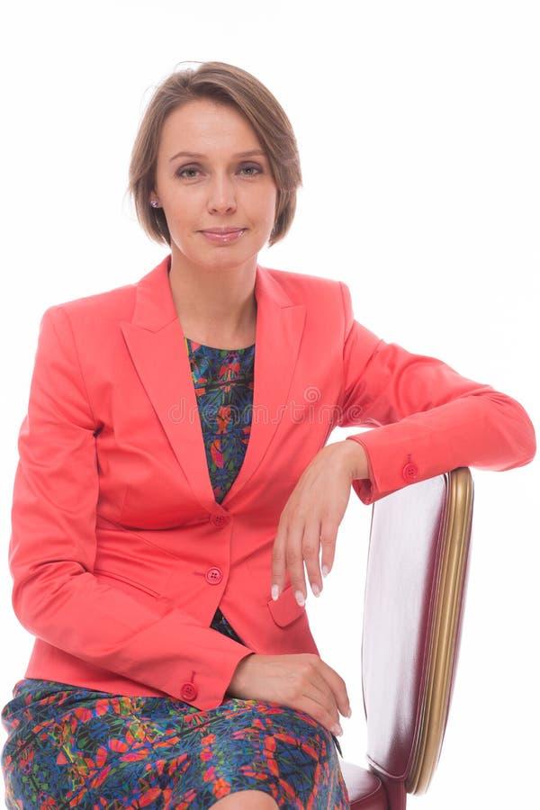 Kvinnan sitter på stol som isoleras med vit fotografering för bildbyråer