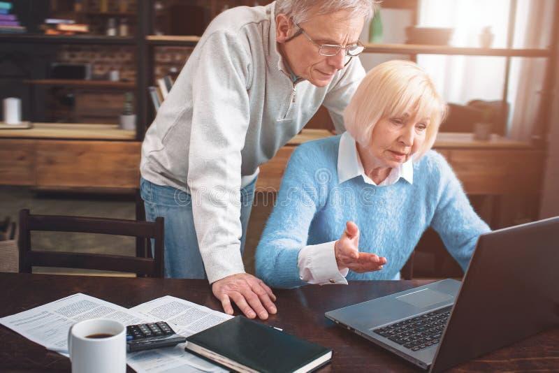 Kvinnan sitter på tabellen och försöker att förstå hur detta arkivfoton