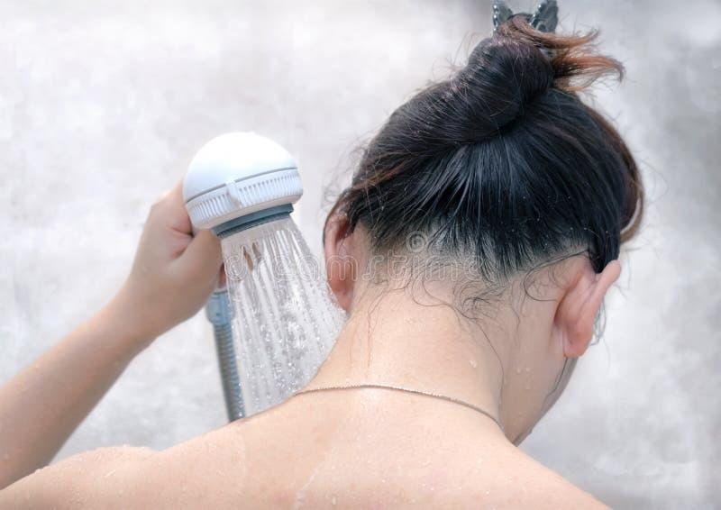 Kvinnan sköljer halsen med en hand - rymt duschhuvud arkivbild