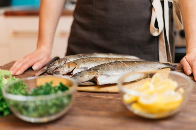 Kvinnan ska laga mat fiskmaträtten i kök royaltyfri fotografi