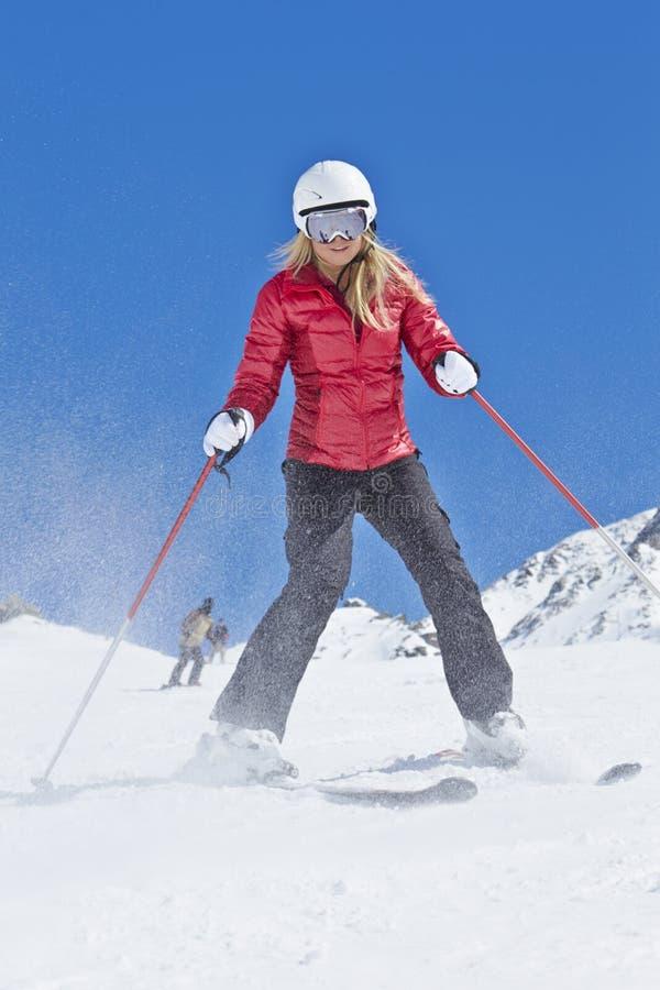 Kvinnan skidar på ferie i berg arkivfoto
